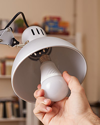 Hand places an energy-efficient lightbulb in a lamp.
