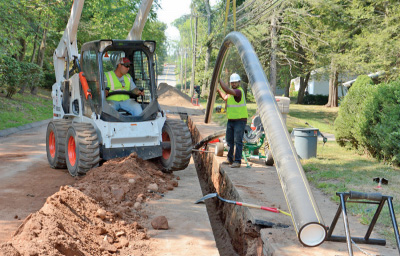 Eversource employees work to install new gas pipes in the street.